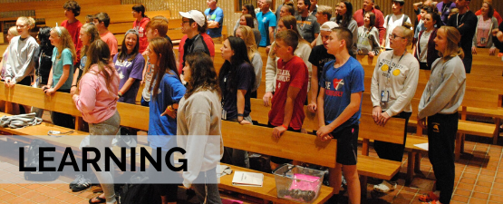 High School  Young Adults in a church on a mission trip large banner