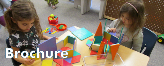 Two children building with mutli-colored blocks at a table large banner