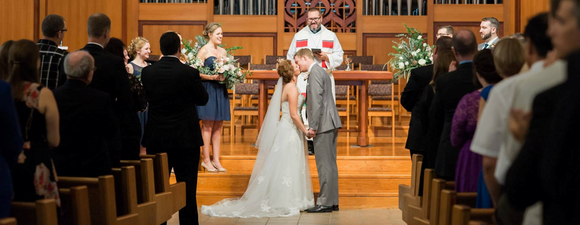 Couple kissing at the altar on wedding day in the Sanctuary large banner